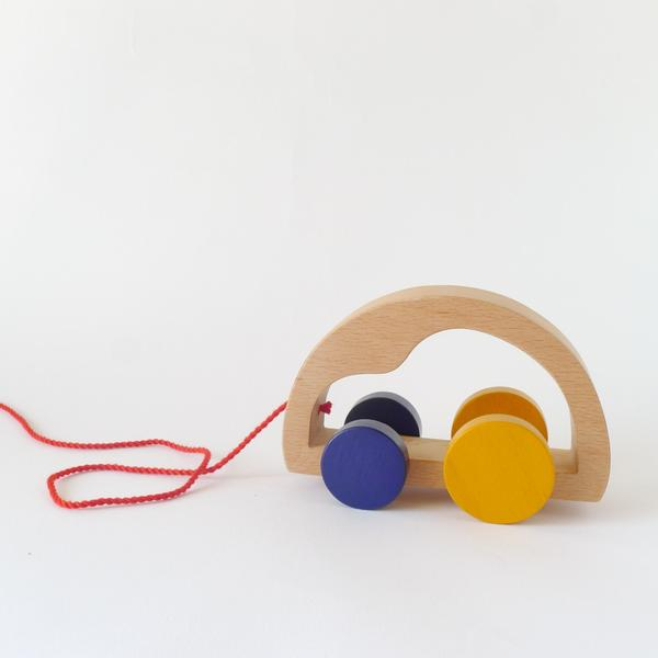 The Wandering Workshop wooden car pull toy with yellow and blue wheels and a red string