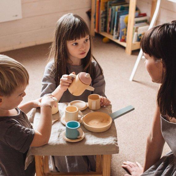 Children playing with Raduga Grez pastel wooden tea set
