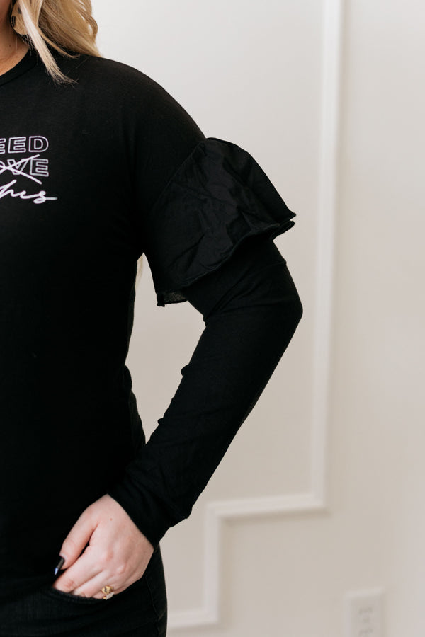 Ruffle sleeve detail, All you need is lashes black long sleeve tee. Model is wearing size Large.