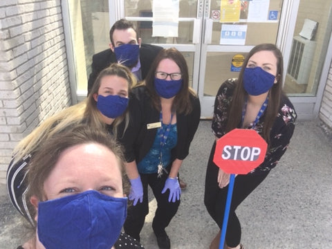 Covergalls employees wearing masks and holding stop sign in support of safe social distancing
