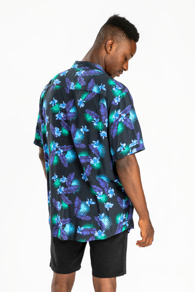 men's short sleeve party shirt by Poolside Party Shirts with blue, green and black tropical leaf print back view