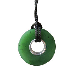 Greenstone doughnut shaped pendant on black cord