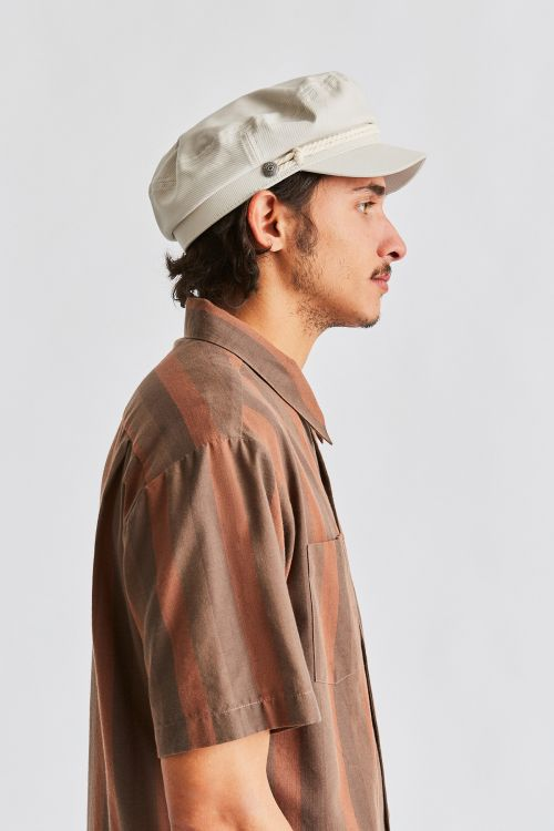 Man wearing Dove coloured Brixton Fiddler cap, side on
