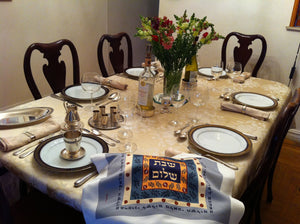 Gorgeous silk challah cover graces this elegant Shabbat table