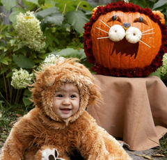 Cute baby wearing lion costume sitting next to pumpkin.