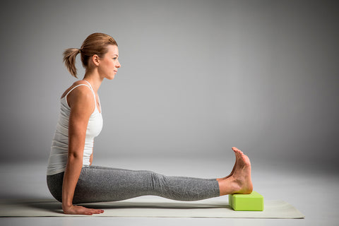 A woman is practicing yoga with a yoga block