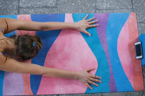 A lady is practicing yoga on a colorful yoga mat