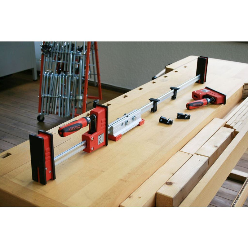 Bessey Clamp Extender attached to two bar clamps to make a longer one
