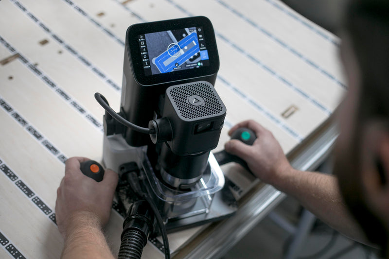 An operator watches the LCD display screen and guides the Origin along the workpiece to machine the programmed design.