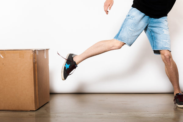 image of a men legs kicking a carton box