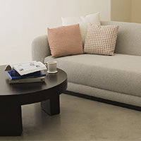 Couch with 3 pillows and table with books and a mug