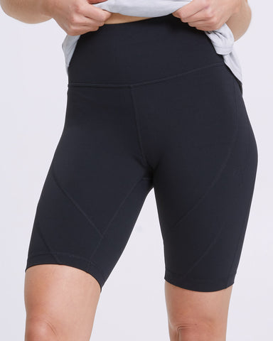 Woman wearing a black Peachymama ultimate comfort postpartum compression shorts