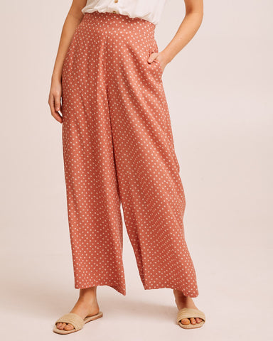 Woman wearing a rust dot Peachymama wide leg postpartum pants