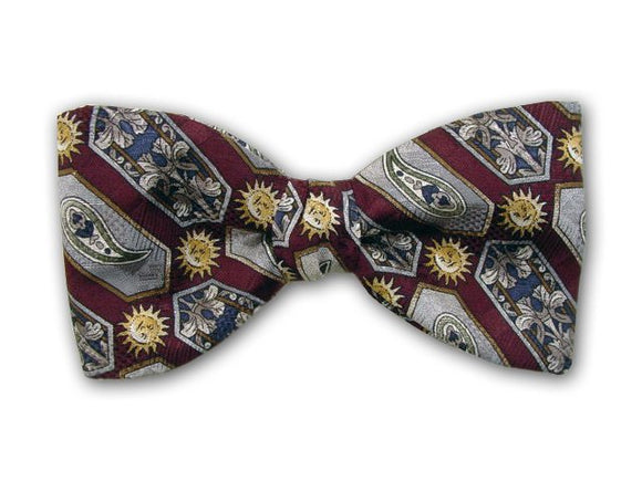 Sun, flowers, paisley, and geometric on burgundy. Silk jacquard bow tie.