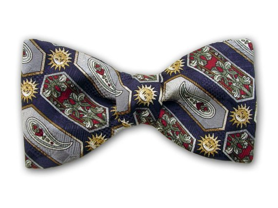 Sun, flowers, paisley, and geometric on navy. Silk jacquard bow tie.