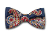 Red, yellow, white, beige and black paisley on blue. Pure silk twill bow tie.