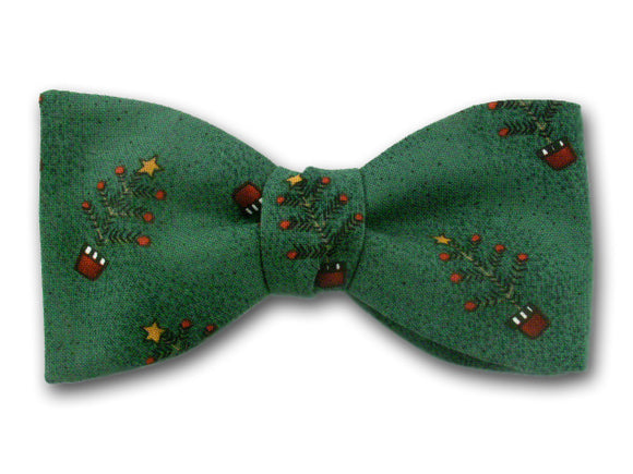 Christmas bow tie with starry tree on green.