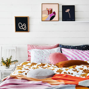 Fern Range by Castle. White Wood Panelled Wall in Bedroom with Rachel Castle Artworks Blush Pretzel and Little petal Flower. Lilac and White Stripe Pillowcase with Pink, Navy and Grey Pillowcases