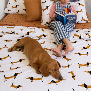 Sausage Dog Flat Sheet by Castle. Butterscotch Linen range. Girl reading on bed with dog