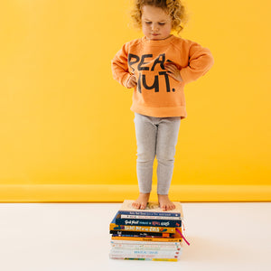 Baby Peanut Sweater by Castle. Child wearing Peanut Sweater Standing on Stack of Books Against Yellow Backdrop