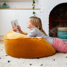 Butterscotch Velvet Floor Cushion by Castle. Girl reading. Pink tights. Black and white spot rug