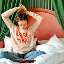Darling Sweater by Castle. Girl sitting on bed twisting her hair
