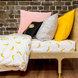 Wooden Bed with Banana Bedding Against Brick Wall by Castle