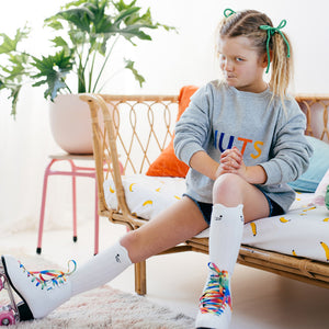 Girl with Piggy Tails sitting down on Rattan Chair Wearing Roller Skates and Nuts Sweater by Castle