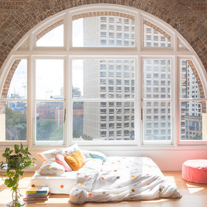 Multi Spot Bedding by Castle. Large Arched Window Overlooking Skyscraper. Open Space Room with Multi Spot Bedding, Baby Pink Velvet Cushion and Green Tree
