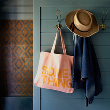 Something Tote Bag by Castle. Hanging on hook with towel and hat