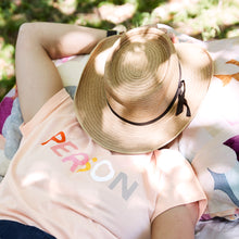 Person Tshirt by Castle. Woman relaxing with Big Hat and Nude Coloured Person Tshirt