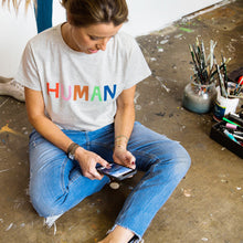 Lady Sitting Down Wearing Blue Jeans on Phone in Human Tshirt By Caslte