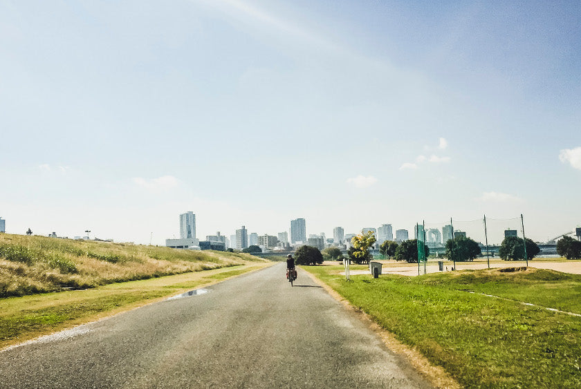 A cyclist riding along the Yodogawa river cycling route in Osaka.