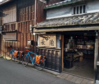 Two touring bikes with panniers leaning against a traditional old Japanese shop and building.