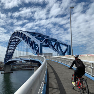 A cyclist about to head over a bridge on riverside cycling route in the Osaka harbor area.