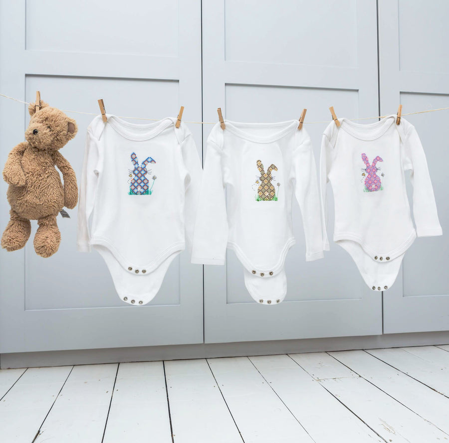 Cross stitch baby gros hanging on a washing line