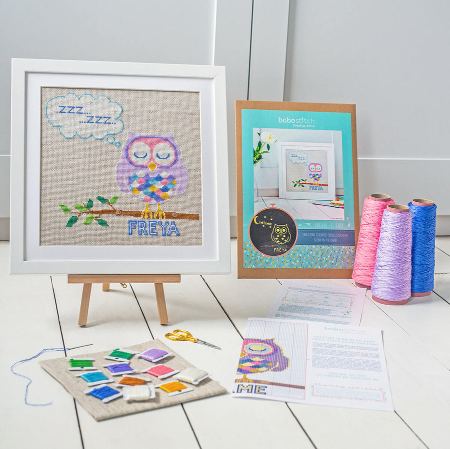 Glow in the dark cross stitch kit shown with DMC threads
