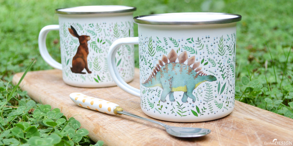 Enamel camping mugs with a botanical print of a stegosaurus dinosaur and a hare.