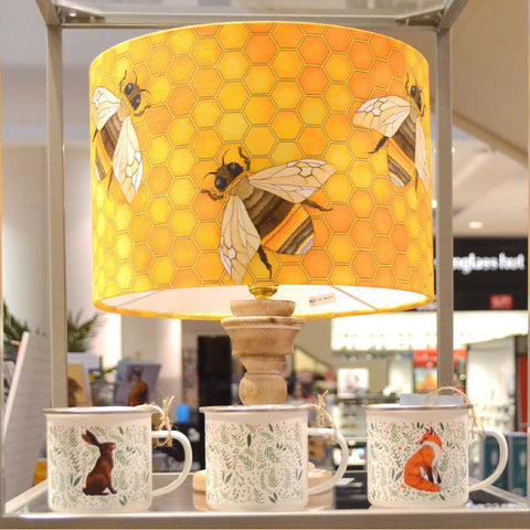 A display of a lampshade with a bee pattern, and three enamel mugs featuring woodland animal prints.