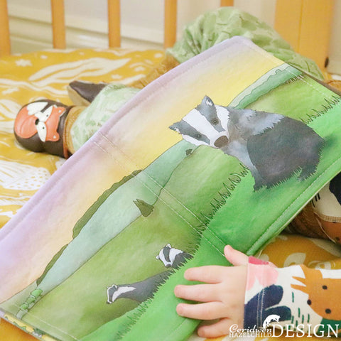 A baby holding a handmade fabric book featuring a badger illustration.