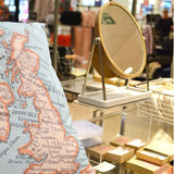 A map cushion by Girl and Bird alongside jewellery by Pouss Design.