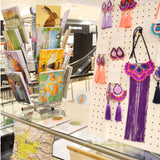 A displayboard of purple and orange jewellery by Dakota Rae Dust and notebooks with woodland animal prints by Ceridwen Hazelchild Design.