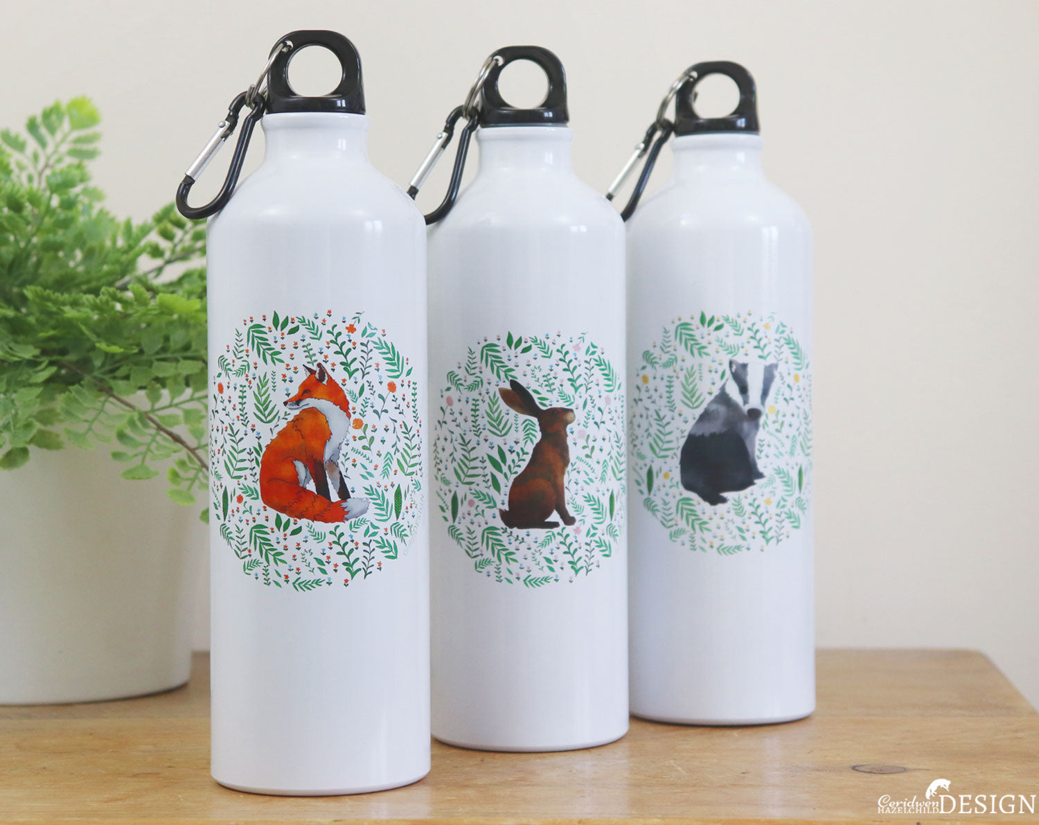 Three water bottles with woodland animal illustrations by Ceridwen Hazelchild Design.