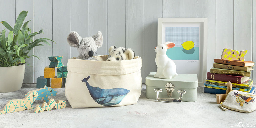 Children's toys with a canvas storage box featuring a whale print by Ceridwen Hazelchild Design.