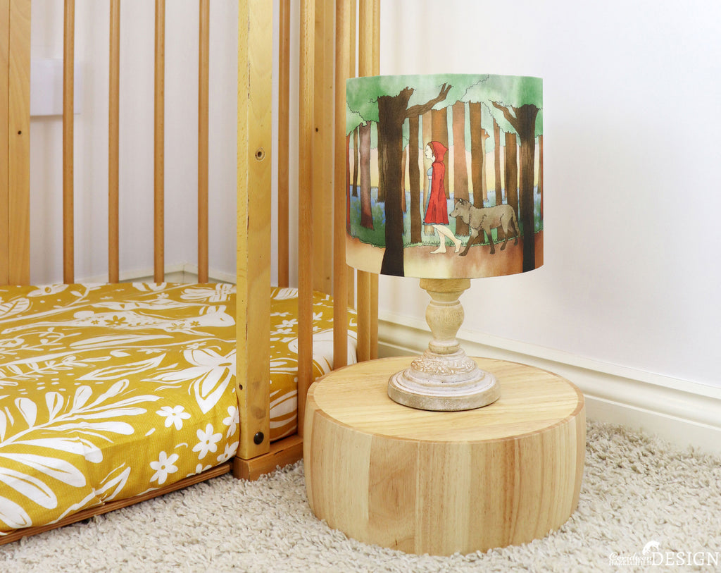A small nursery bedside lamp featuring a Little Red Riding Hood illustration by Ceridwen Hazelchild.