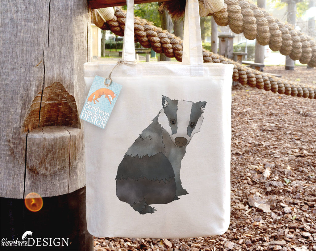 A cotton tote bag with a print of a badger on the front, hanging from a wooden climbing frame.