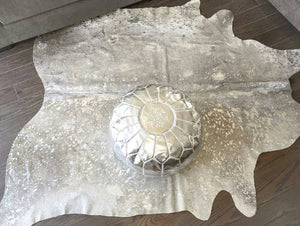 metallic cowhide rug and leather poufs hand in hand.