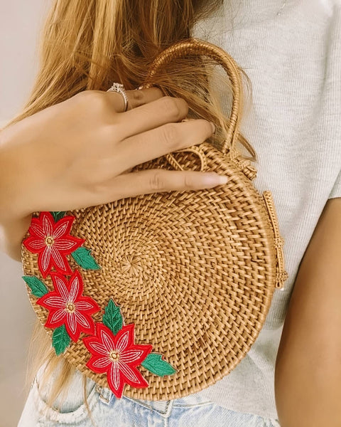 Round rattan bag with handle and beautiful flower embroidery.