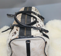 A beautiful speckled cowhide luggage bag great for weekend getaway it has inner pockets, metal zippers and detachable leather handle.