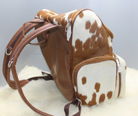A natural cowhide backpack is made for mommies who love shopping, this southern style bag is made from real fur in speckled brown and white.